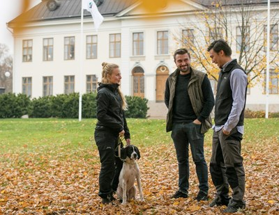 Two male students and one female student with a dog outside a building in Skinnskatteberg, photo.