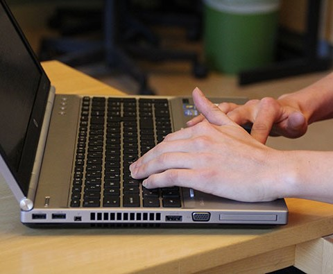 Close up of a person's hands and a laptop, photo.